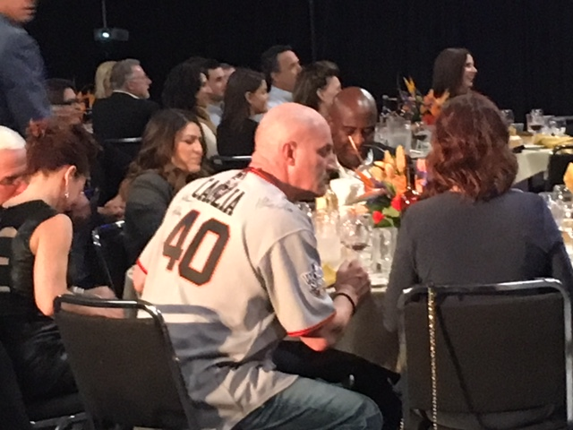 State Center Trustee Richard Caglia shows off his Giant fandom at the Fresno Grizzlies Hot Stove  dinner on Feb. 1, 2018. Fresno City Council President Esmeralda Soria and businessman Terance Frazier are in the background. (photo: David Taub)