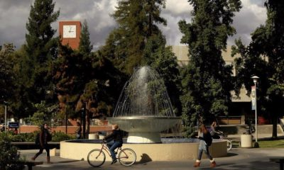 Students walk and cycle past the centerpiece fountain at Fresno State