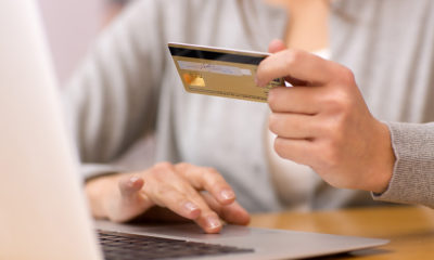 Online Sales - Woman makes credit card purchase using laptop computer