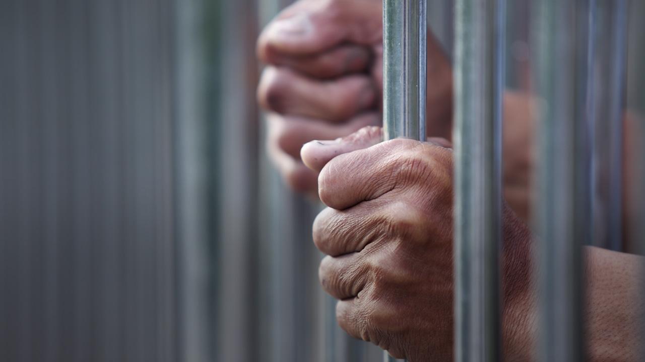 Prisoner hands gripping jail cell bars