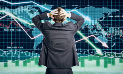 Picture of a man with his hands on head because he's puzzled by contradictory financial indicators