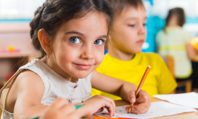 Photo of a girl and a boy at a table in a preschool room