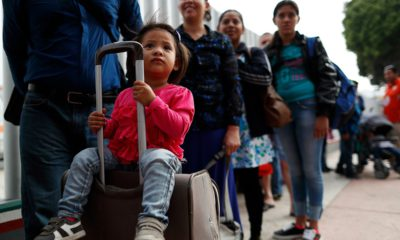 Photo of people waiting to cross into the U.S. to begin the process of applying for asylum