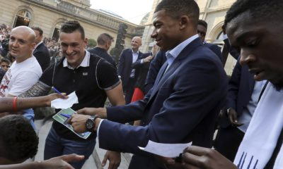 Photo of two French World Cup team members signing autographs