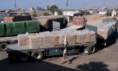 Photo of Palestinian worker next to cargo trucks