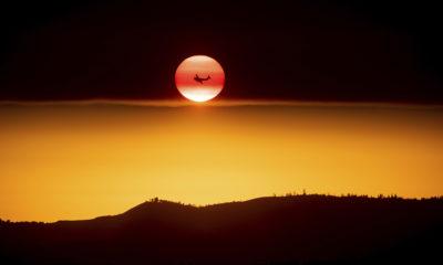 Photo of plane fighting the Ferguson Fire passing a setting sun