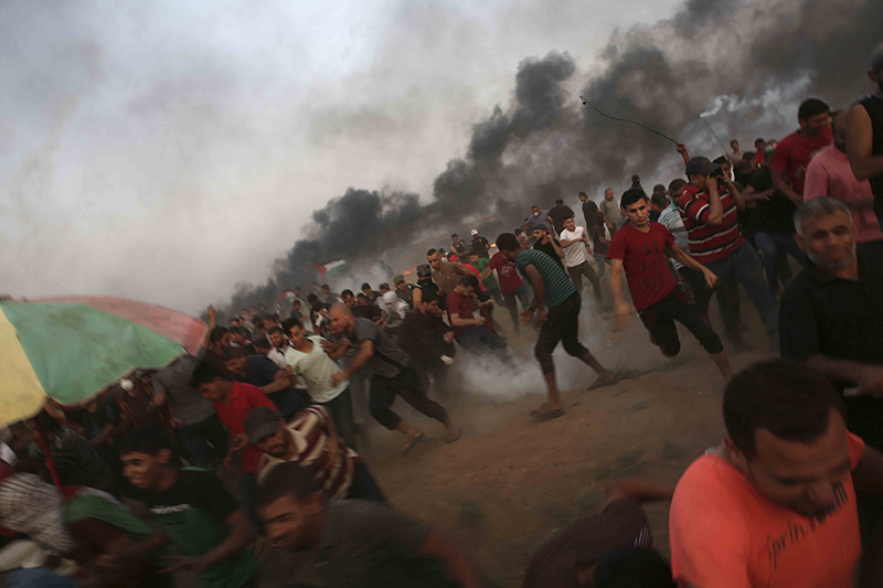 Photo of protesters running from tear gas at the Gaza Strip border