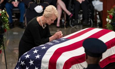 Photo of Cindy McCain leaning over John McCain's casket