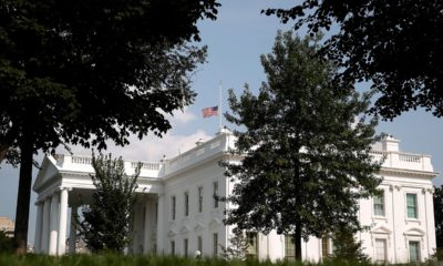 Photo of the American flag flying half-staff at the White House in Washington