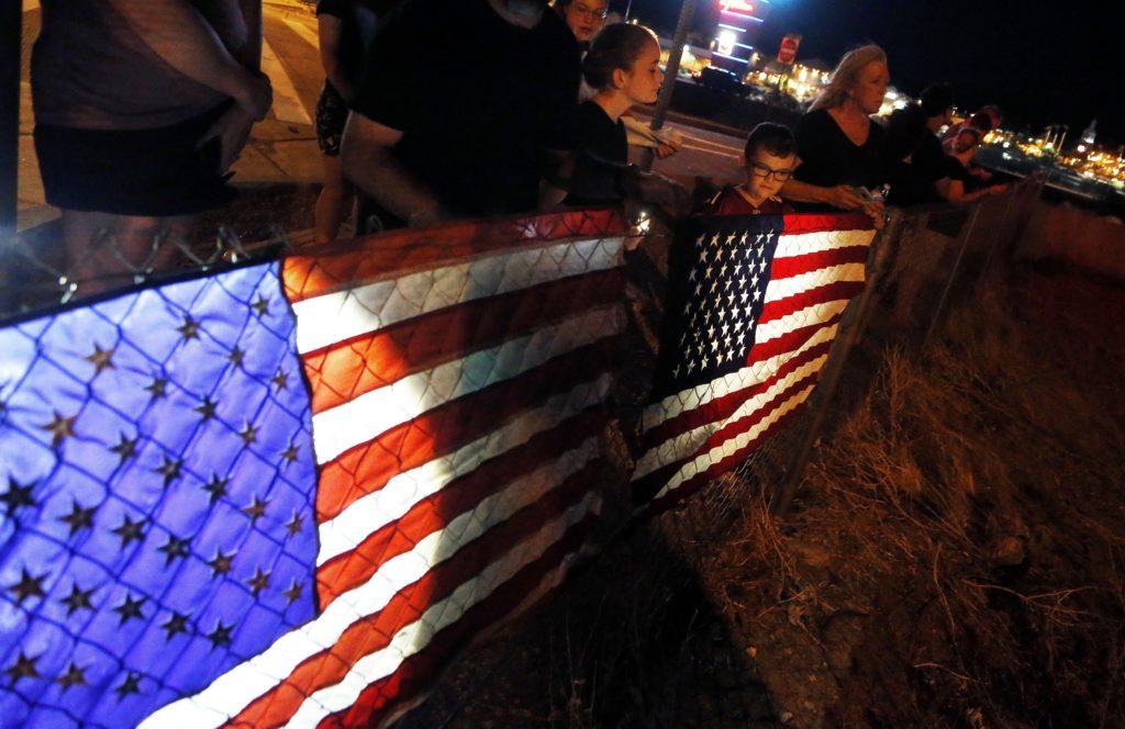 Photo of citizens lining street at night to honor John McCain