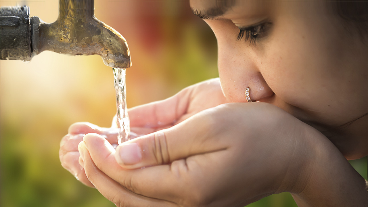 Young person drinking from an outdoor water faucet