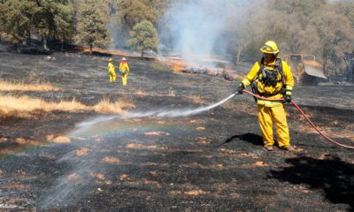 Photo of firefighters spreading water on smoldering spots