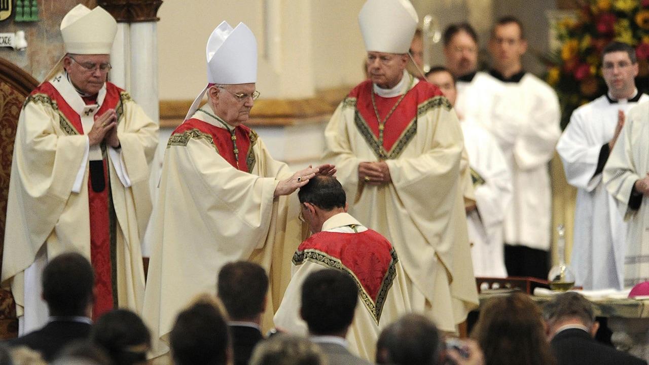 Photo of retiring bishop kneeling and praying