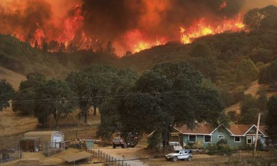 Wildfire burns on hills above rural home.