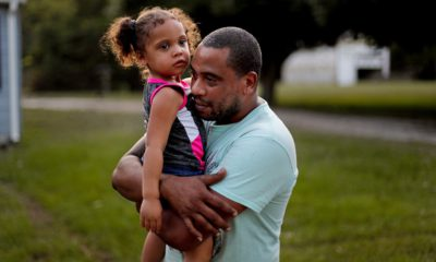 Photo of Jose Perez-Santiago, right, holding his daughter Jordalis, 2, as they return to their home for the first time since it was flooded