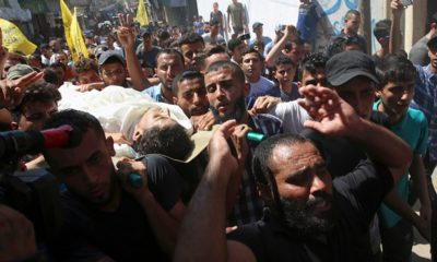 Photo of mourners chanting while carrying the body of Ahamd Omar