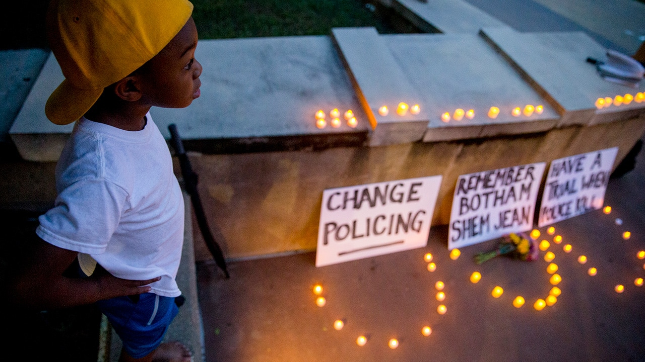 Photo of Solomon Grayson, 6, stands on a ledge next to a memorial
