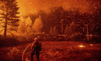 Photo of embers flying around a firefighter