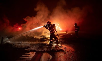 Photo of a firefighter spraying the remains of a vehicle