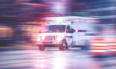 Photo of ambulance racing through city streets on a rainy night