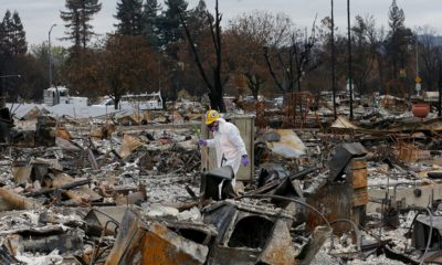 Photo of work crews removing debris at the site of a home destroyed by fires in the Coffey Park