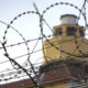 A prison guard tower viewed through razor wire fencing