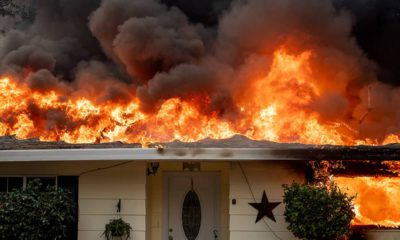Photo of a home burning in Paradise, California.