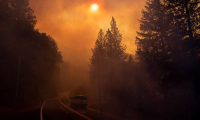 Photo of a car driving through smoke from a wildfire in Pulga, CA