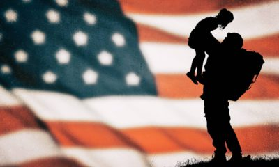 Photo of an American flag with a soldier and child silhouette