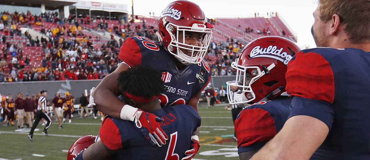 Photo of Fresno State defensive back Anthoula Kelly holding up game MVP running back Ronnie Rivers
