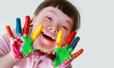 Photo of young girl with down syndrome showing off her painted hands