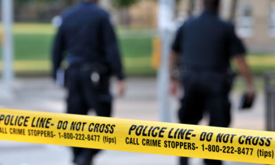 Photo of crime scene tape and two police officers