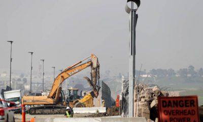 Photo of crews working to demolish border wall prototypes