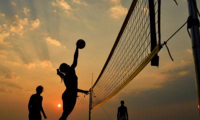 Photo of women playing beach volleyball