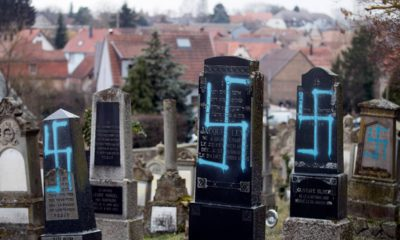 Photo of gravestones vandalized with swastikas