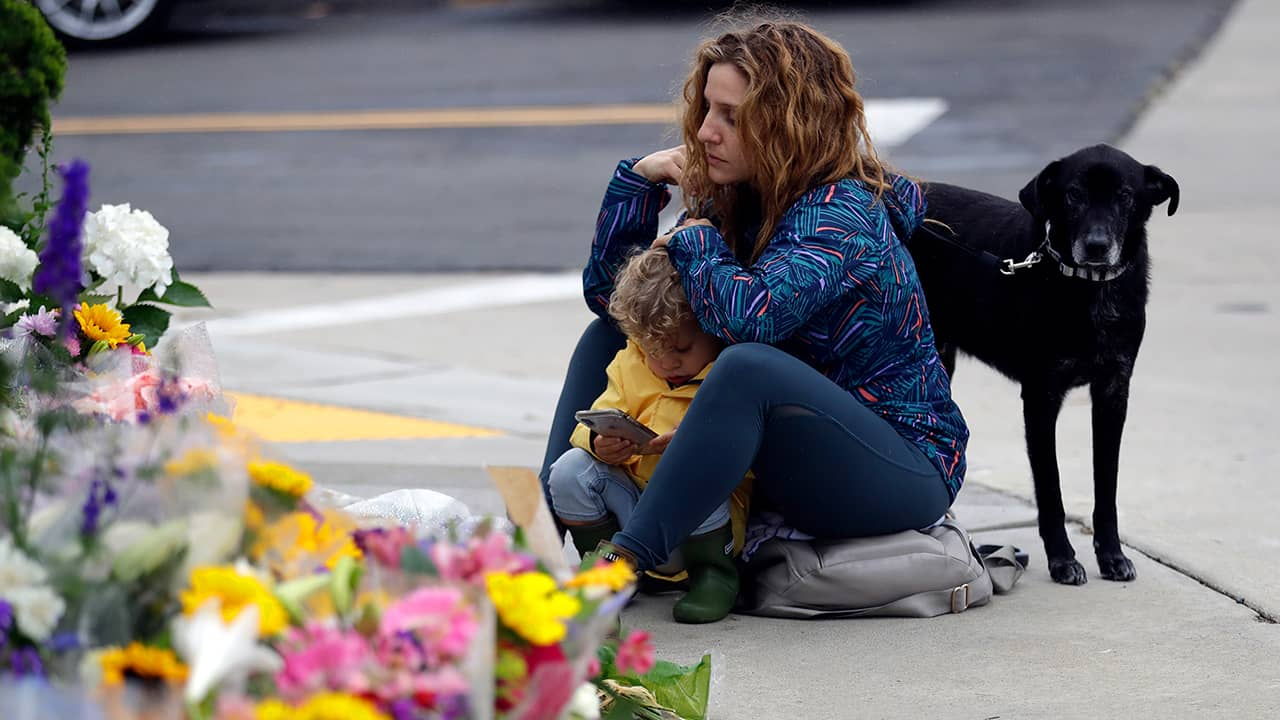 Photo of woman sitting at a memorial for the Chabad of Poway synagogue