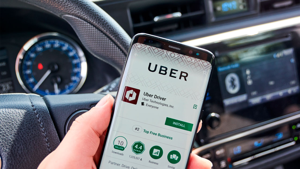Uber driver inside car with ridesharing app displayed on smartphone.