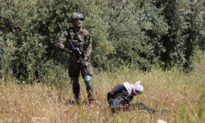 Photo of an Israeli soldier standing over handcuffed and blindfolded Osama Hajahjeh