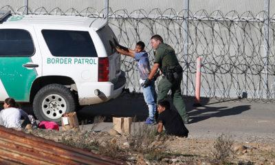 Photo of asylum seeker being taken into custody by US Border Patrol