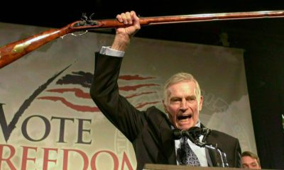 Photo of National Rifle Association President Charlton Heston holding up a rifle