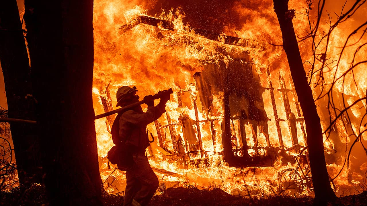 Photo of firefighter Jose Corona spraying water at flames