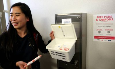 Photo of UC Davis student working to ensure placement of tampons and pads in UC Davis restrooms