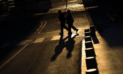 Photo of elderly couple walking across a street