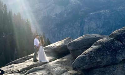 Photo of a couple at Yosemite's Glacier Point bathed in a ray of sunlight