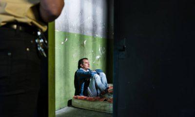 Photo of a prisoner sitting on a mattress