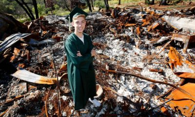 Photo of Sean Newsom posing at the burnout remains of his home in Paradise, CA