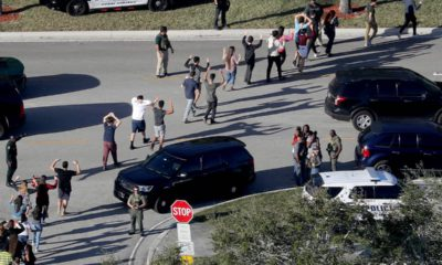 Photo of students holding their hands in the air as they are evacuated in Parkland, Fla.