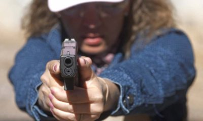 Photo of school secretary aiming a pistol at a shooting range