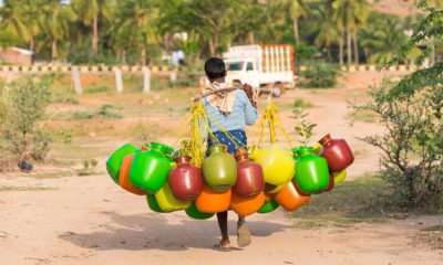 Photo of an Indian boy carrying jugs of water