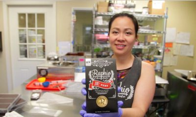 Owner of Raphio Chocolate Factory holds up a bag of chocolate